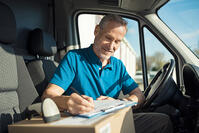 delivery man in van with checklist