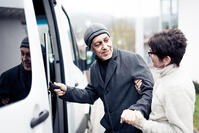 nurse helping senior man into van
