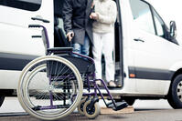 person helping man out of wheelchair van - shutterstock_742009000