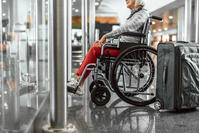 senior woman in wheelchair with luggage