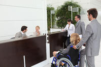 woman in wheelchair at hotel reception
